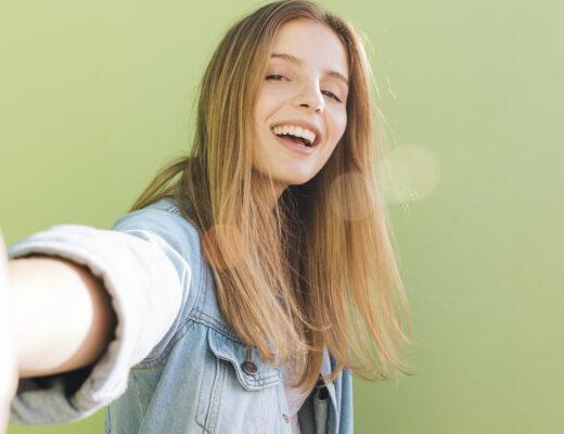 młoda dziewczyna uśmiecha się do obiektywu, selfie